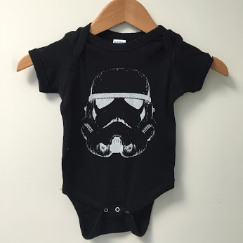 stars wars onsie featuring storm trooper helmet.
