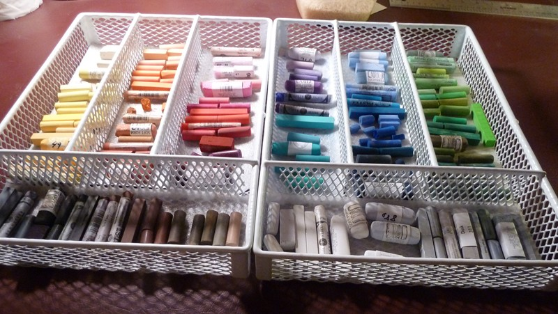 Pastels organized in a silverware or flatware divider.