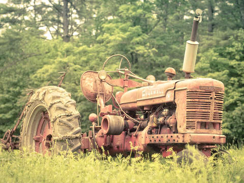 MH20- Old Farmall tractor in the field by Edward M. Fielding
