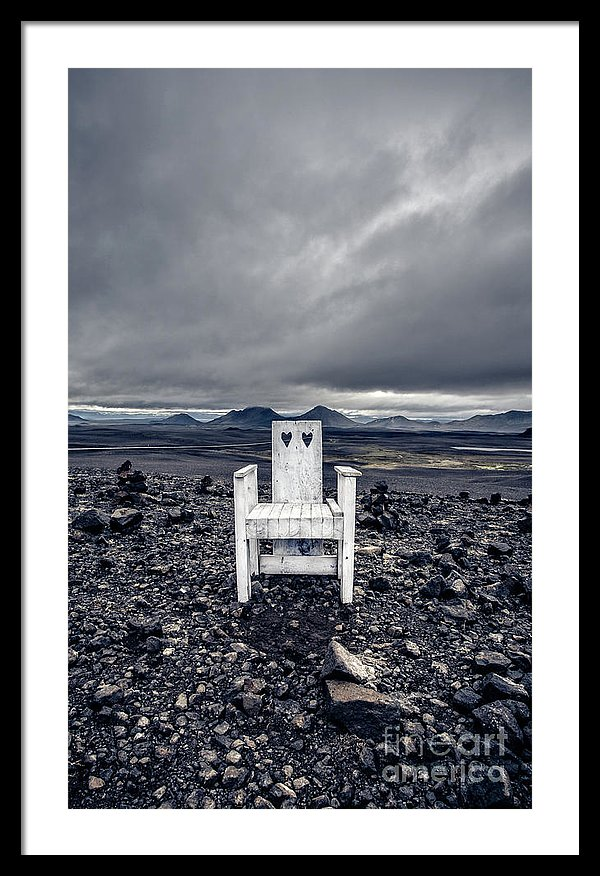 iceland: single white chair in the middle of a black lava flow